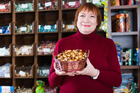 mature woman buyer choosing chocolate candies in the food store