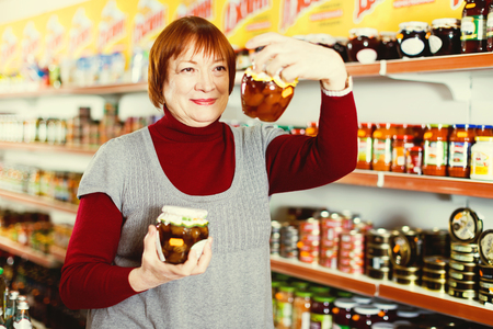 mature woman  choosing canned jar of jam at the supermarket Фото со стока - 118443406