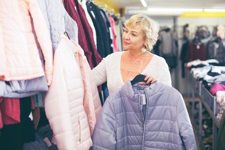 Adult female consumer choosing windbreaker jackets in the shopping center
