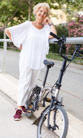 Portrait of retired woman resting near bike after ride in park Фото со стока - 118450606