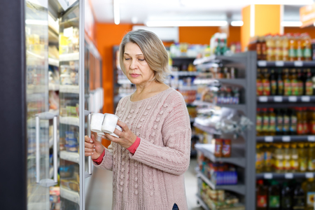 Casual mature woman shopping for milk products at supermarket food department