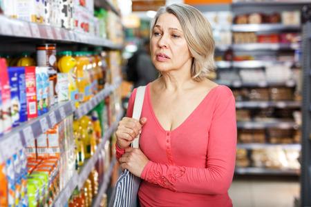 Pensive senior female shopping at shop, walking among shelves and choosing products Stock Photo