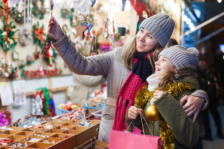 Woman and her daughter are preparing for Christmas and choosing gifts for their family outdoor.