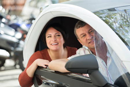 Portrait of happy man and woman standing near twizy electric outdoors Banco de Imagens