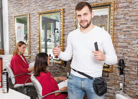 Cheerful male hairdresser  standing in beauty studio, clients on background Stock Photo