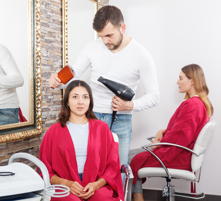 Man professional hairdresser styling and drying hair with fen of woman in salon