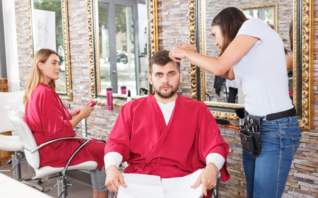 Young female hairstylist working with  male's hair  in hairdressing salon