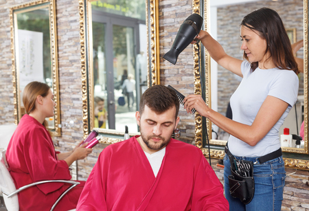 Young woman  hairstylist drying hair with blow dryer of guy  in salon Stock Photo