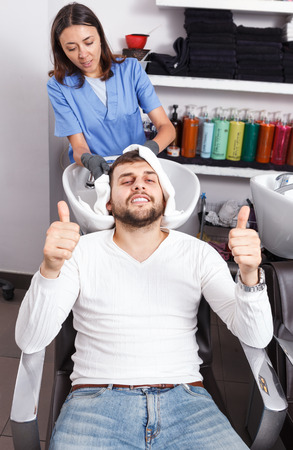 Female professional washing cheerful male's hair in  barbershop