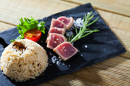 Delicious slightly fried tuna (tataki) served with spicy rice and citrus base soy sauce on black serving board