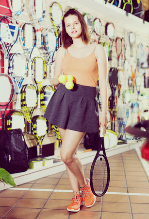 Young smiling glad positive female standing in sporting goods store with balls and racket