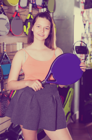 Smiling young woman holding professional racket for tennis in sport shop