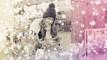 Young smiling girl choosing Christmas decoration at market Imagens