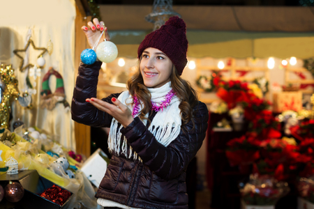 Happy woman choosing Christmas decoration at market in evening time Stock Photo - 118549474