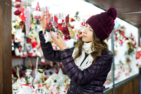 Beautiful young girl choosing Christmas decoration at market in evening time
