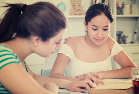 Two girls classmates sitting at table at home and doing homework together