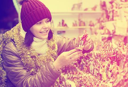 Positive girl  buying figures and workpiece for creating Christmas