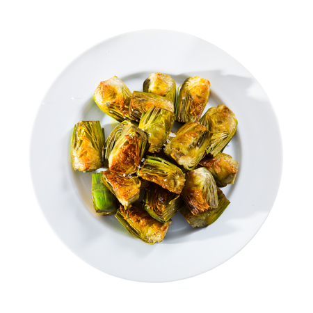 Plate of tasty roasted in oil organic artichokes. Isolated over white background Archivio Fotografico