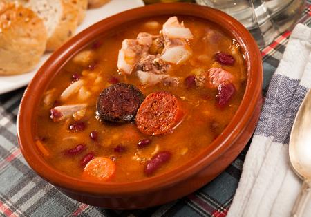 Fabada asturiana – beans stewed with chorizo and bacon served on clay pot Stock Photo