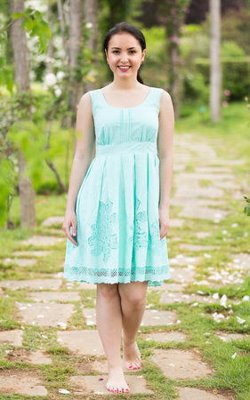 portrait of young cheerful  female in  dress  near roses in a outdoors