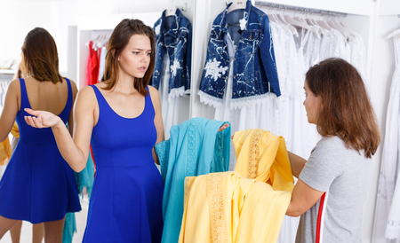 Girl expressing her indignation about quality of clothes to sales consultant in boutique