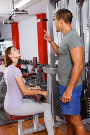Personal instructor helping young woman with exercise technique at gym Stockfoto