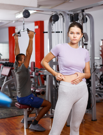 Upset girl pinching skin of her belly at gym Фото со стока