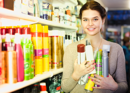 cheerful woman customer deciding on hair care products in cosmetics shop