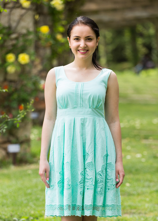 portrait of young positive european  woman in  dress  near roses in a garden Stock Photo