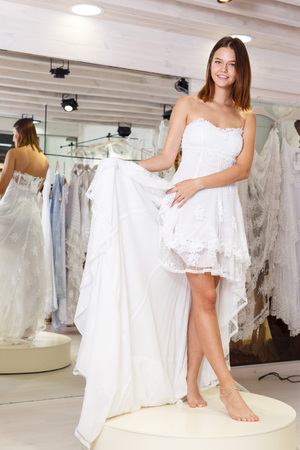 Young happy girl fitting wedding dress at modern wedding salon
