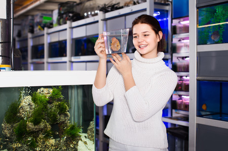 happy girl holding plastic container with big colorful fish breed Discus in aquarium shop