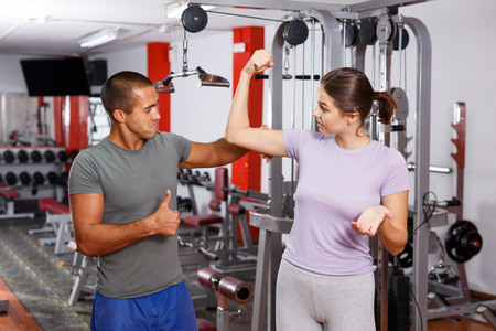 Young sporty man and woman talking emotionally at gym Фото со стока