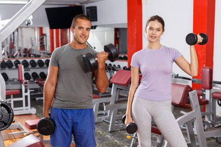 Happy sporty guy and girl posing with sports dumbbells at gym