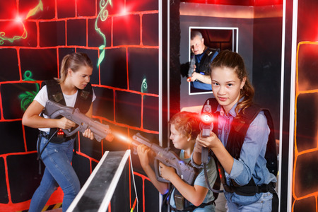 Emotional teen girl with laser pistol playing laser tag with family on a dark labyrinth