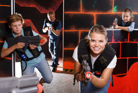 Happy children and parents aiming laser guns  during lasertag game in dark room Фото со стока