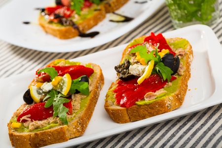 Sandwich with canned tuna, guacamole, olives, arugula and Feta cheese is tasty dish in the kitchen. Zdjęcie Seryjne