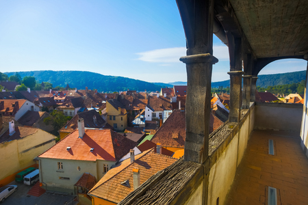View from clock tower of Sighisoara tile roofs in sunny autumn day, Romania Banco de Imagens