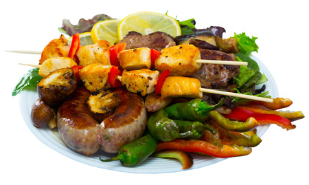 Plate of dish bulgarian cuisine meshana scara with different grilled meat and vegetables. Isolated over white background