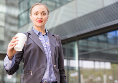 Professional woman employee in jacket with coffee standing outdoors Stockfoto
