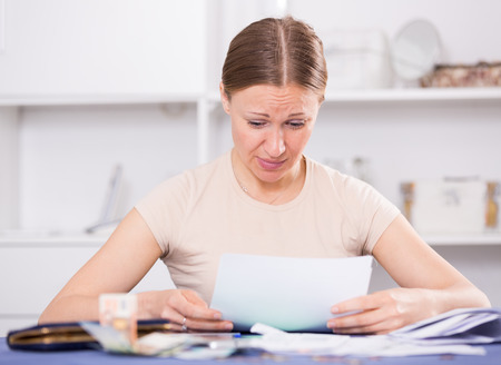 Woman sitting at table and looking worriedly at bills Фото со стока