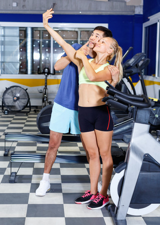 Smiling glad friendly  athletic pair making selfie during break in workout session at gym Stockfoto