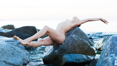 portrait of relaxation  young nude female at  sunset sea shore Banque d'images