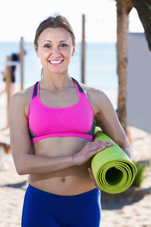Portrait of positive sportswoman with gym mat on the beach