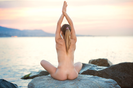Positive nude female meditating in yoga position lotos in a seaside