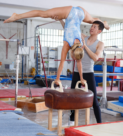 Athletic man and woman training on pommel horse in acrobatic hall Foto de archivo - 118821695