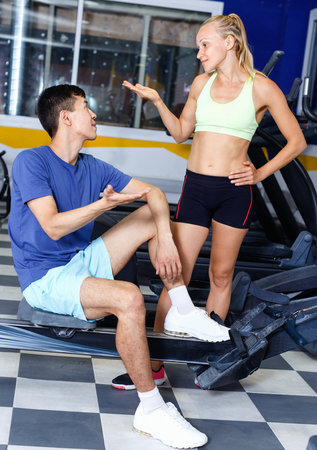 Couple of sporty smiling  friendly  people relaxing on break during indoor fitness workout Фото со стока