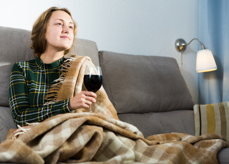 Portrait of young woman sitting at home with glass of wine Imagens