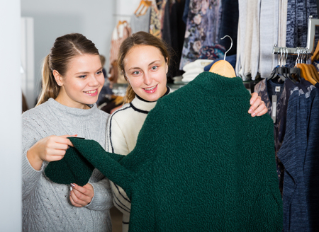 Portrait of two young attractive women choosing new overcoat in clothing store Фото со стока - 118823924