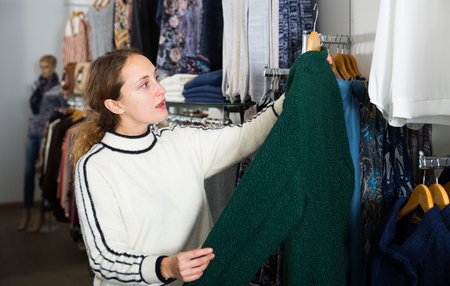 Young cheerful woman shopping in outerwear clothing boutique 写真素材