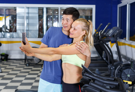 Cheerful sporty couple taking selfie during workout in fitness center Stock Photo
